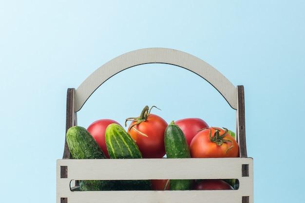 파란색 배경에 토마토와 오이가 있는 나무 상자. 야채의 신선한 작물입니다. 프리미엄 사진