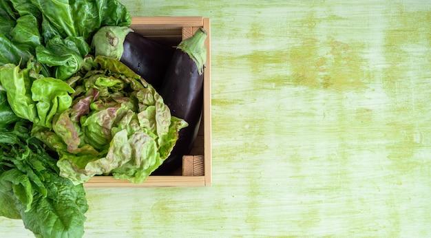 緑の木製の背景に野菜と木箱。コピースペース。コンセプト野菜。
