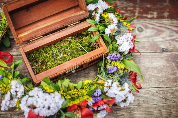 Wooden box with wedding rings in flowers