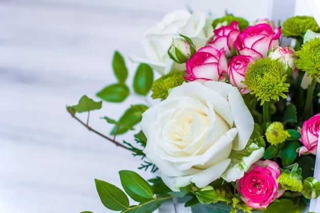 白い木の板に白とピンクのバラと菊が入った木箱。家の装飾。フラワーボックス。結婚式の装飾