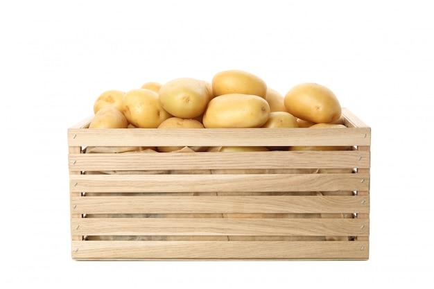 Деревянная коробка с молодой картошкой на белой поверхности
