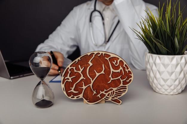 Деревянный мозг и песочные часы в кабинете врача. концепция времени и ранней диагностики.