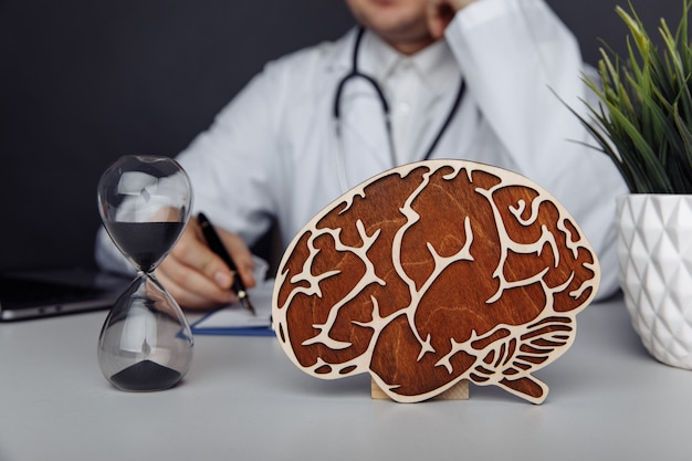 Wooden brain and hourglass in doctors office.