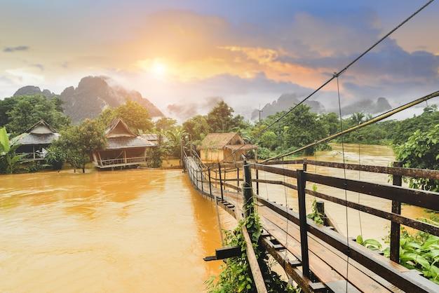 Деревянный мост через плавучую реку с солнечным освещением.