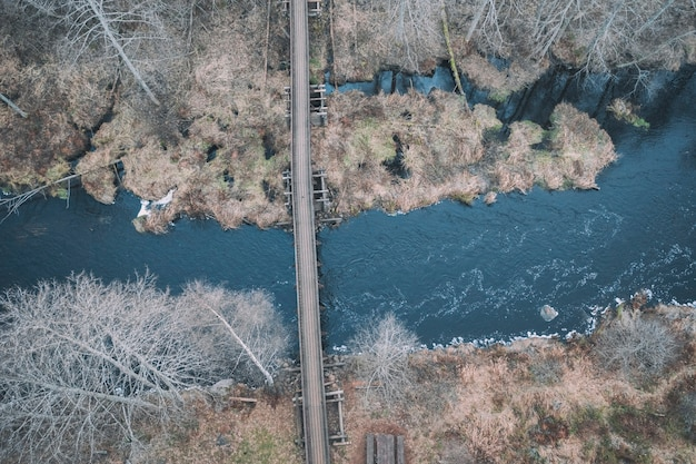 Wooden bridge over the blue river in the autumn forest. aerial view