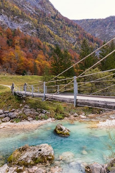 Wooden bridge over clear turquoise soca river in slovenian alps in autumn season