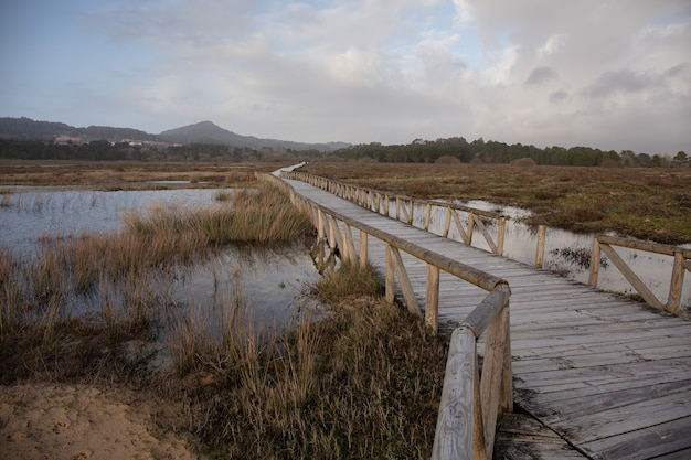 Wooden bridge on a lake in a field surrounded by hills under a cloudy sky