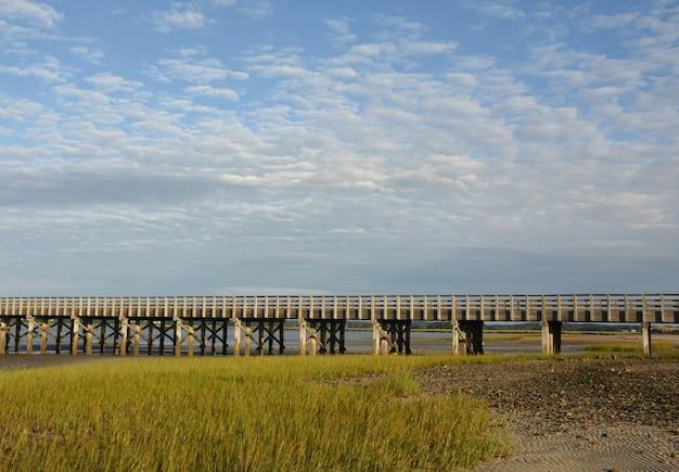Деревянный мост через залив с болотной травой во время отлива