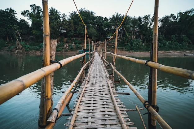 Деревянный мост через реку нам хан в луангпхабанге, лаос. старый опасный мост из бамбука. перспективный вид