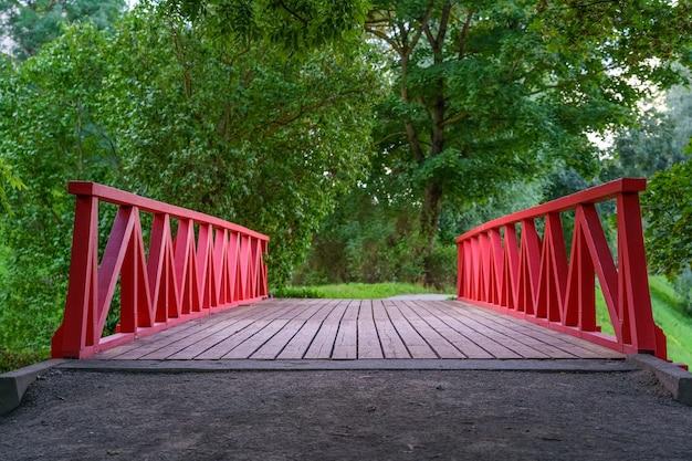 녹지로 가득한 공공 공원에서 강 위에 있는 목조 다리.