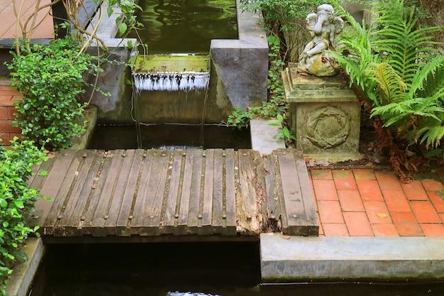 Деревянный мост через пруд с фонтаном в саду