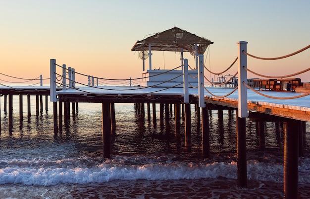 Деревянный пирс моста против красивого неба
