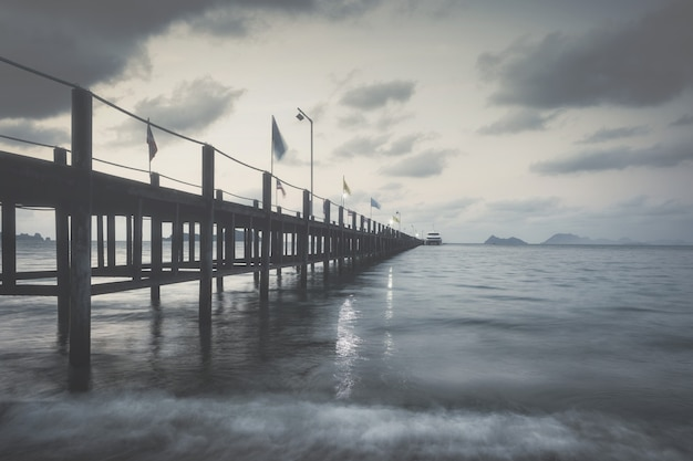 Wooden bridge on the sea on a rainy day