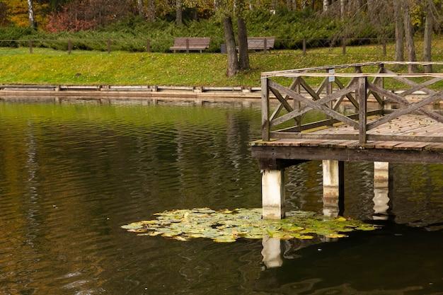 Деревянный мост со смотровой площадкой над озером. осенний вид.