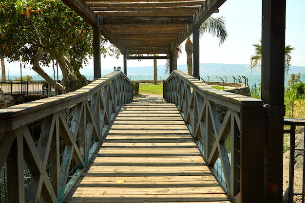 Wooden bridge with a roof on the sea of galilee, july