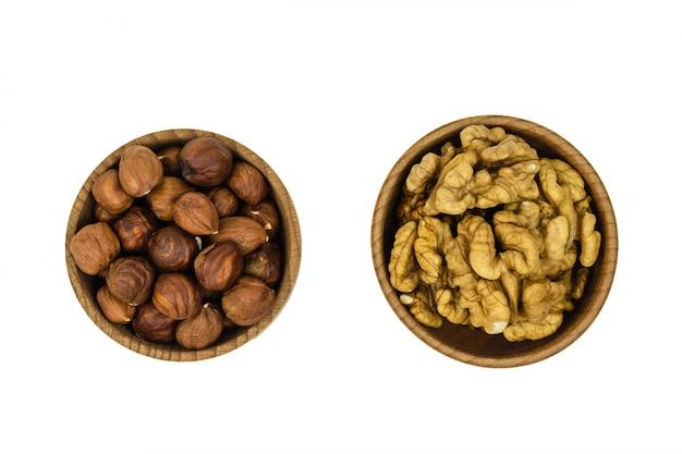 Деревянная коричневая миска с лесными орехами и изолированными орехами вид сверху.