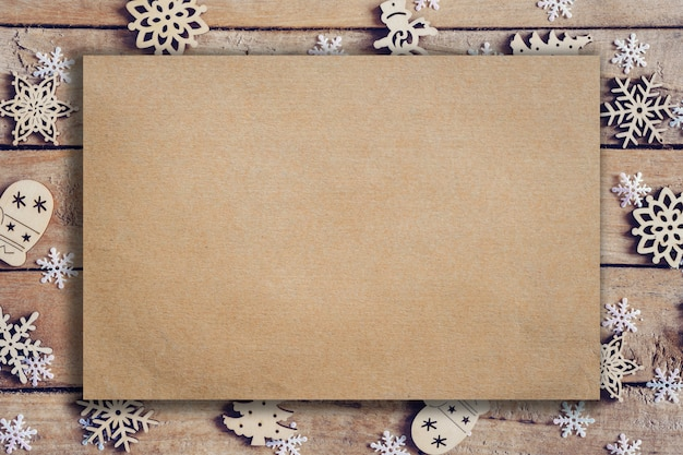 Wooden brown christmas background with snowflakes and old brown paper with space.