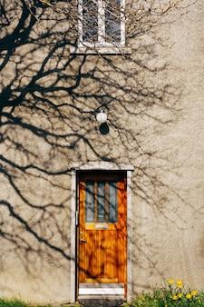 窓の下の建物に長方形の窓があり、常夜灯のある茶色の木製ドア