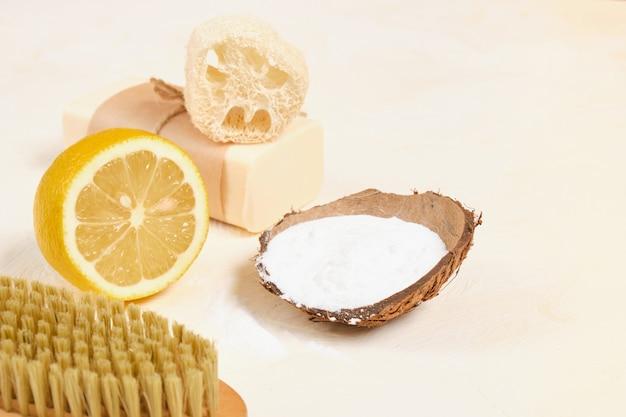 ゼロウェイストのライフスタイルコンセプトをエコクリーニングするための木製ブラシ、レモン、石鹸、ヘチマ、重曹。ハウスキーピング用の無毒洗剤
