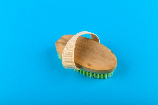 Wooden brush massager. massage wooden soft body brush with natural pile, worn on the hand, on a blue background, used in the
