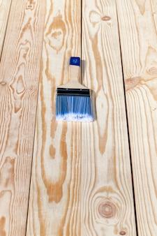 소나무 나무 바닥을 칠하기위한 파란색 강모가있는 나무 브러시