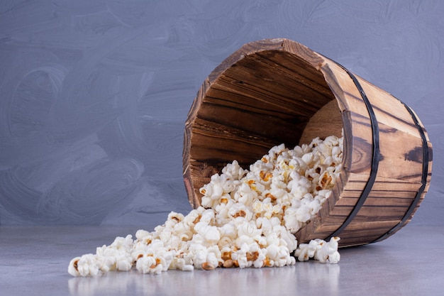 Wooden bucket fallen over, spilling out popcorn on marble background. high quality photo