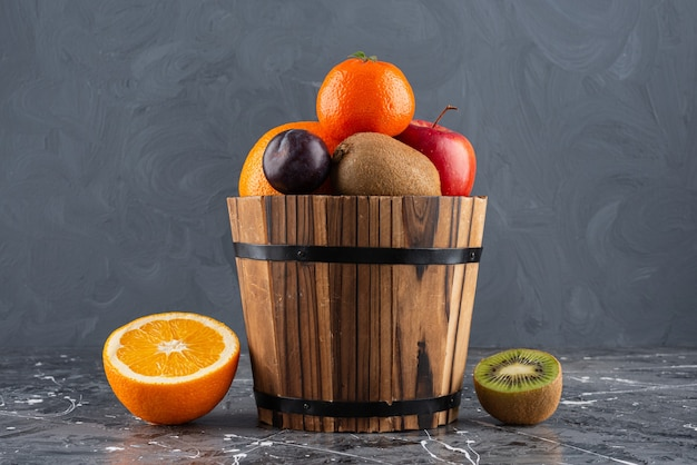 Wooden bucket full of fresh fruits on marble surface.