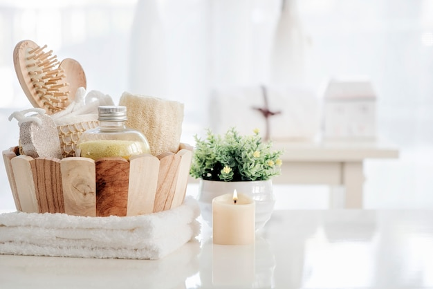 Wooden bucket with spa accessories on white table.
