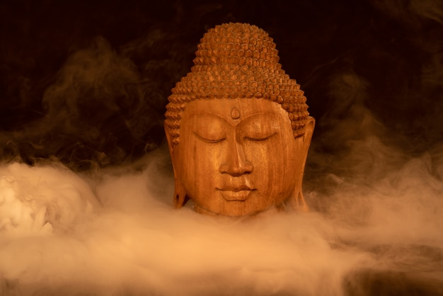 Wooden buddha head in warm colors against black with misty smoke