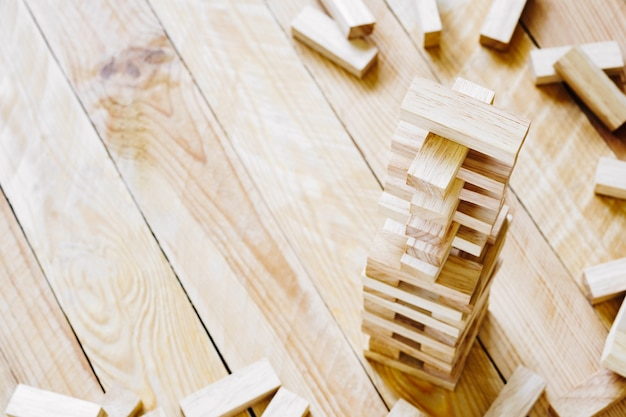 Wooden building blocks tower on wood background with copy space.
