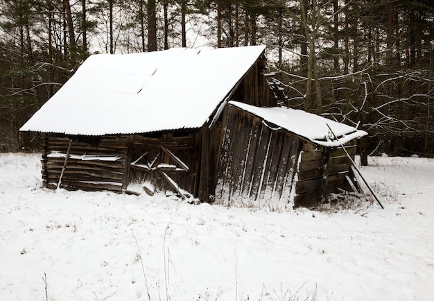 A wooden building covered with snow in the winter time