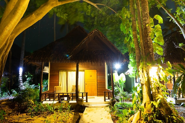 Wooden bungalow in the forest house at night in the jungle tall green tropical trees