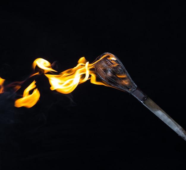 Деревянный горящий факел на черном фоне