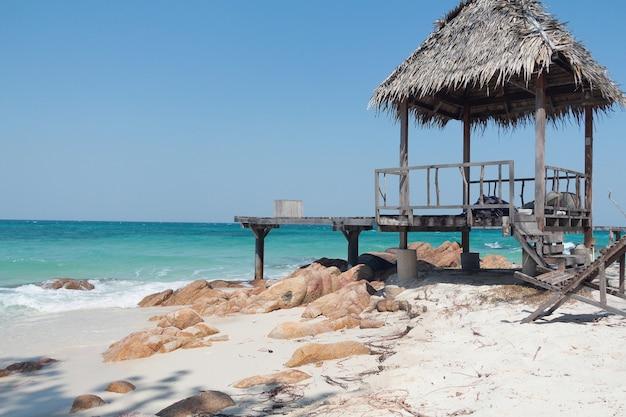 熱帯のビーチに桟橋と木製のカバナ。