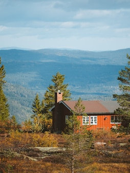 A wooden cabin in a forest with beautiful rocky mountains in the background in norway
