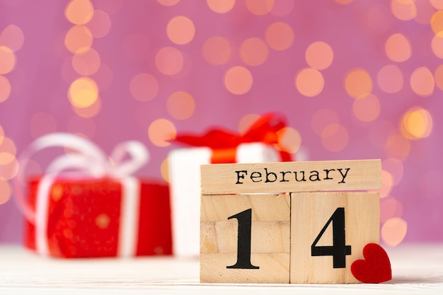 Wooden calendar 14th of february on pink bokeh front view