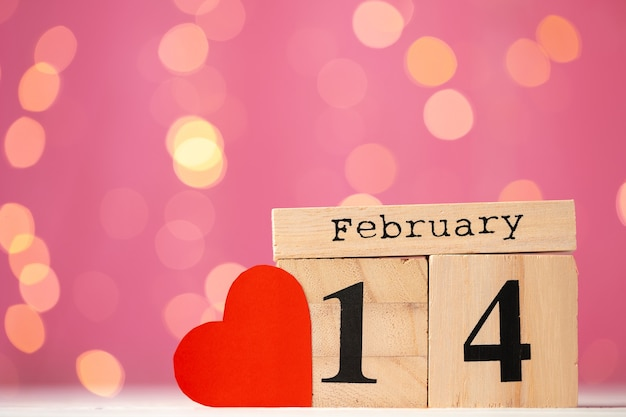 Wooden calendar 14th of february on pink bokeh