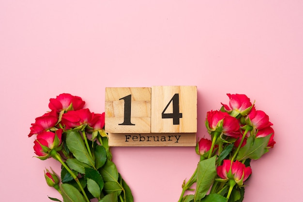 Wooden calendar 14th february and roses on pink flat lay