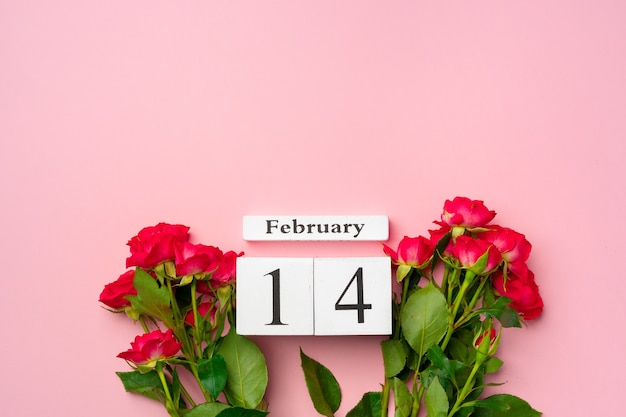 Wooden calendar 14th february and roses on pink