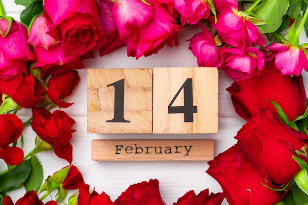 Wooden calendar 14th february and roses on white flat lay