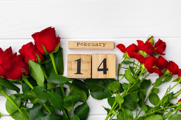 Wooden calendar 14th february and roses on white