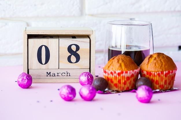木製のカレンダーとテーブルの上にお菓子とコーヒーのカップ。 3月8日の国際女性デーのお祝い