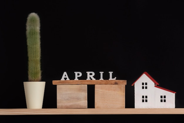 Wooden calendar of april , cactus and house model on black background. copy space.