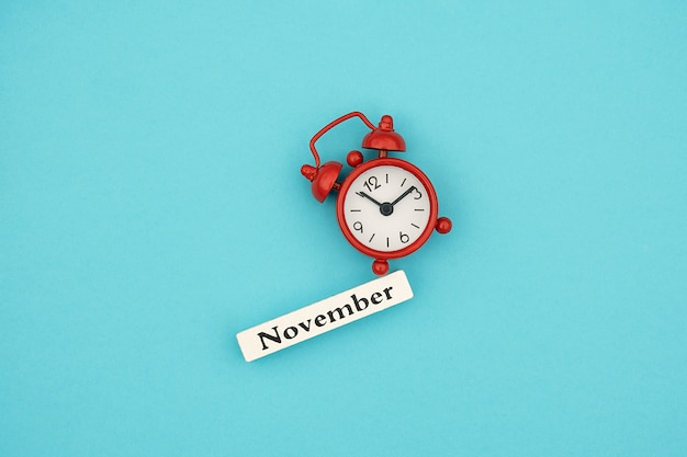 Wooden calendar autumn month november and red alarm clock on blue paper background.  hello september