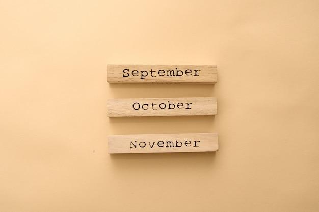 Деревянные календарные осенние месяцы на деревянных кубиках.