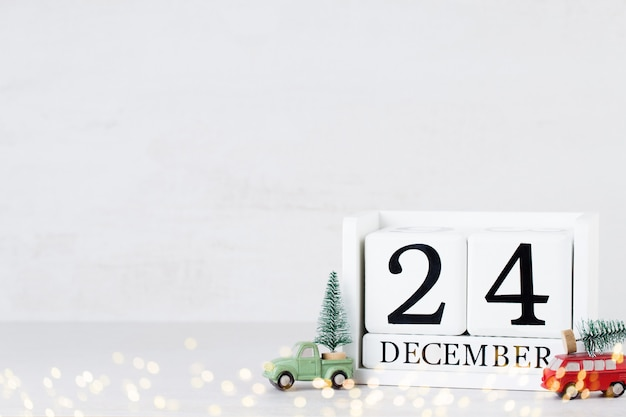木製カレンダー12月24日のクリスマスの日。クリスマスの装飾が施されたグレー。
