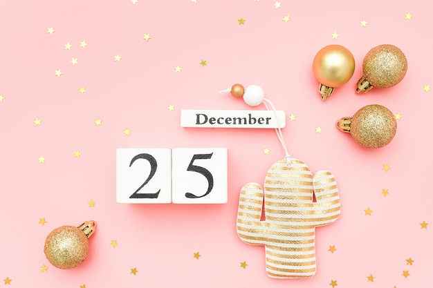 Wooden calendar december 25, gold textile christmas cactus and stars confetti on pink background.