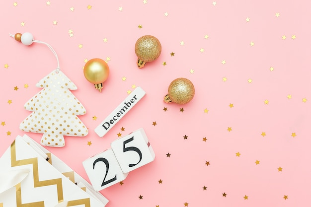 Wooden calendar december 25, textile christmas tree, golden baubles, stars confetti on pink. merry christmas concept.