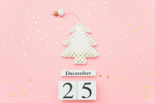 Wooden calendar december 25, textile christmas tree and stars confetti on pink
