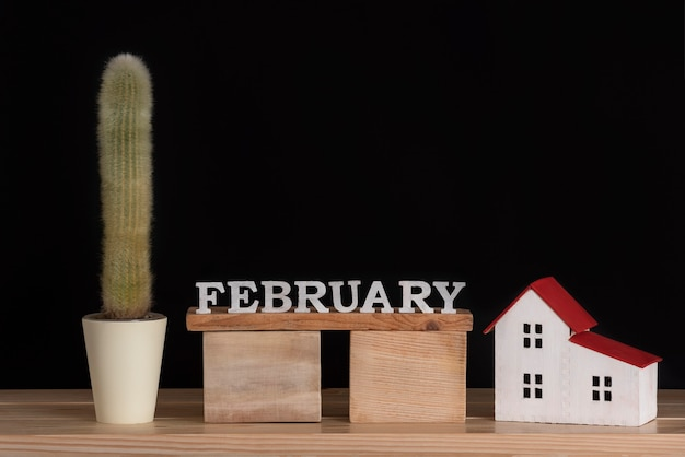 Wooden calendar of february, cactus and house model on black. copy space